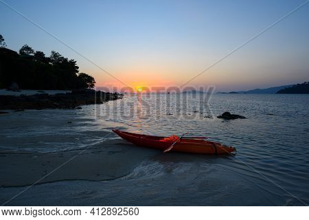 Scene Of Beautiful Sunset At Lipe Island, Satun Province,thailand. Canoe And Life Jacket On The Beac
