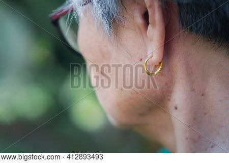 Side View Of The Face Of An Elderly Woman Wearing A Golden Earring. Elderly And Health Care Concept.