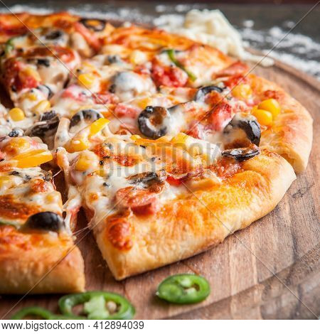 Side View Pizza With Chopped Pepper In Board Cookware On Dark Background