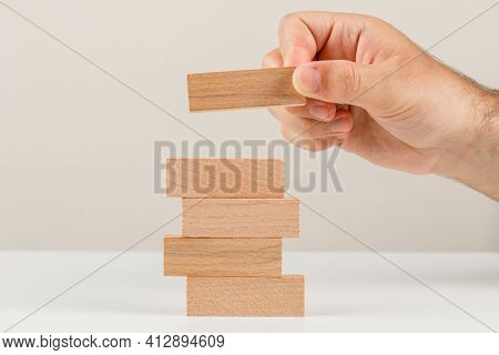 Business Planning Concept On White Backgroud Side View. Hand Placing Wooden Block On Tower.