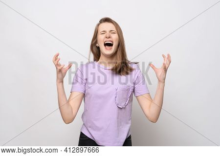 Screaming, Hate, Rage. Angry Teenage Girl Screaming With Aggressive Expression And Arms Raised. Angr