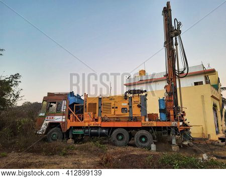 Closeup Of Borewell Drilling Lorry Or Vehicles With Tools, Pipe, Machine And Working Labour And Puja