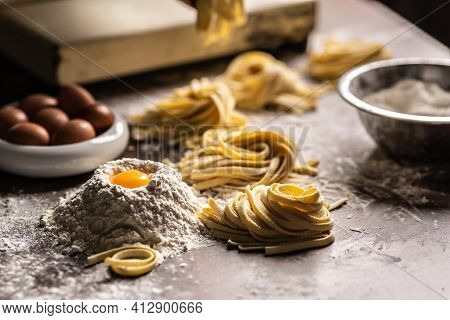 Nests Of Fresh Fettuccine Pasta With Eggs, Egg Yolk, Flour On A Kitchen Prep Table.
