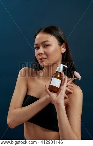 Young Asian Brunette Girl With Face Roller And Skin Care Product. Brunette With Beautiful Body Posin