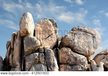 Closeup of a boulder formation in Joshua Tree National Park with blue cloudy sky.