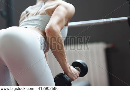 Sportive Woman Stands In Rack Doing Exercises With Dumbbells