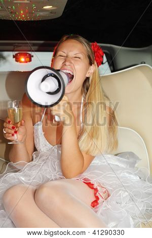 Young beautiful bride sits in car, holds glass of champagne and shouts into megaphone. Pink wedding. Focus on tongue of roof of mouth.