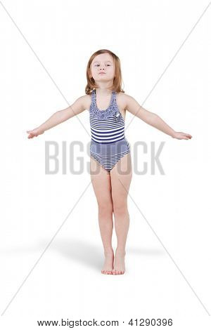 Little girl in striped swimsuit poses standing with her arms outstretched to sides