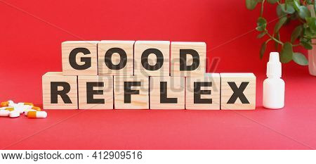 The Words Good Reflex Is Made Of Wooden Cubes On A Red Background With Medical Drugs.