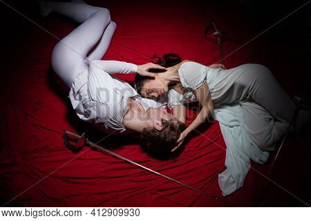 Novel. Young And Graceful Ballet Dancers On Red Cloth Background In Classic Action. Art, Motion, Act