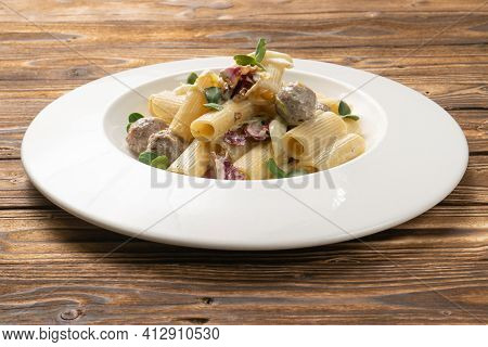 Rigatoni Pasta With Meatballs And Bechamel Sauce In A White Ceramic Plate