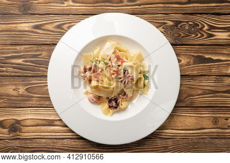 Pappardelle Pasta With Octopus And Bacon In A White Ceramic Plate