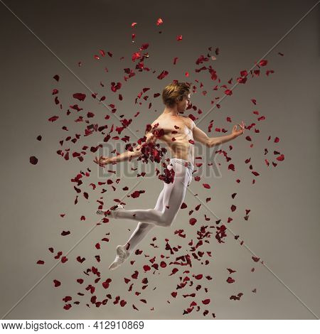 Romance. Young And Graceful Ballet Dancer On Studio Background In Flight, Jump With Rose Petals. Art