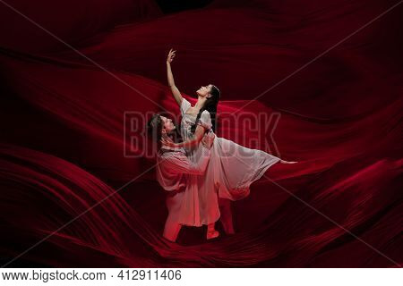 Passionate. Young And Graceful Ballet Dancers On Red Cloth Background In Classic Action. Art, Motion