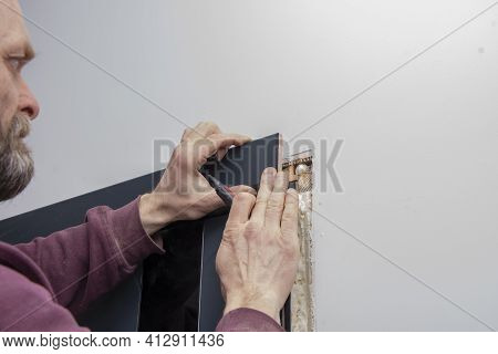 45-50-year-old Male Construction Worker Marks Out The Trim On The Wooden Doors With A Pencil; Concep
