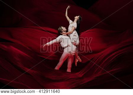 Wine. Young And Graceful Ballet Dancers On Red Cloth Background In Classic Action. Art, Motion, Acti