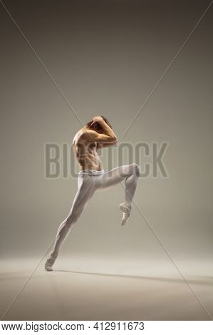Courageasly. Young And Graceful Ballet Dancer Isolated On Studio Background In Flight, Jump. Art, Mo