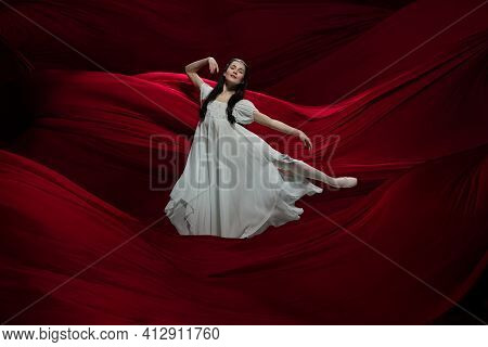Heart. Young And Graceful Ballet Dancer On Flying Red Cloth Background In Classic Action. Art, Motio