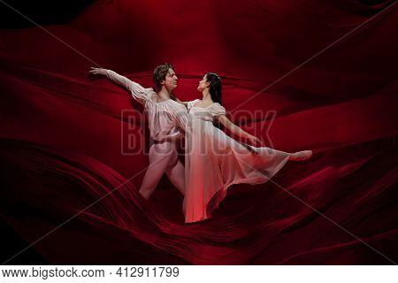 Bordo. Young And Graceful Ballet Dancers On Red Cloth Background In Classic Action. Art, Motion, Act