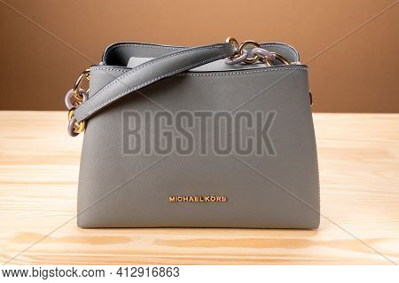 Moscow, Russia - March, 17, 2021: New Model Leather Grey Handbag Michael Kors On Wooden Table. Micha