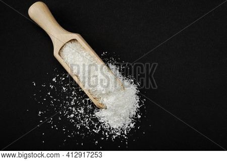 Coconut Shavings. Wooden Scoop Spoon With Coconut Shavings On Black Background. Copy Space. Shredded