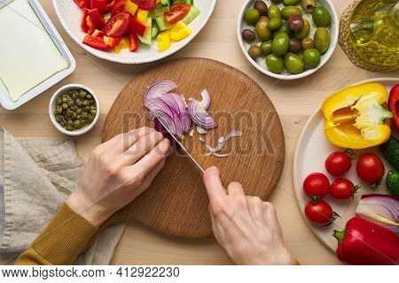 Vegetarian Food. Chopping Onion, Cutting Vegetables For Greek Salad Horiatiki. Woman Hands With Knif