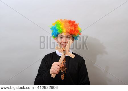 Catholic Pastor In A Clown Wig With A Cross And Rosary. The Concept Of Mockery Of Sectarianism And F