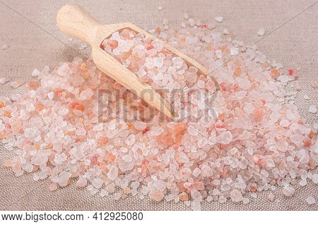 Pink Himalayan Salt. Close-up Himalayan Pink Rock Salt In Wooden Spoon On Black Background. Top View