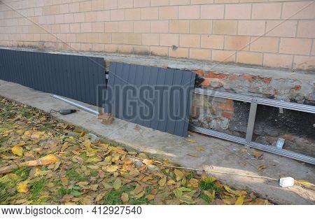 Old Foundation Renovation By Installing Vertical Steel Siding, Metal Siding On A Starter Strip To Pr