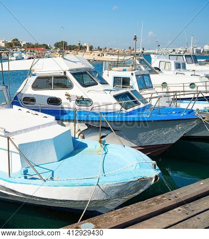 Motorboats In Marina Of Larnaca In Bright Sunshine, City Embankment In Background, Cyprus