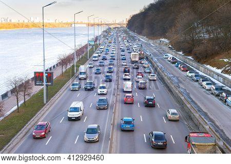 Kyiv, Ukraine - March 03, 2021: Traffic On Embankment Road At Sunset. Kyiv Is The Capital Of Ukraine