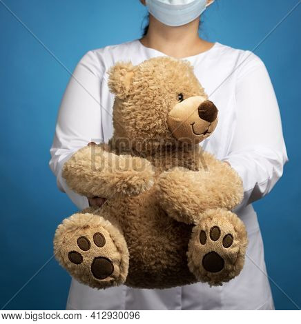 Woman Doctor Pediatrician Holds Brown Teddy Bear, Concept Of Preventing Epidemics And Pandemics Agai