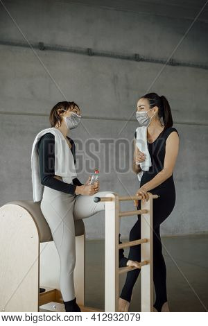 Sporty Women With Face Masks, Sport Clothing, Water Bottle And Towels, Talking And Laughing Before S