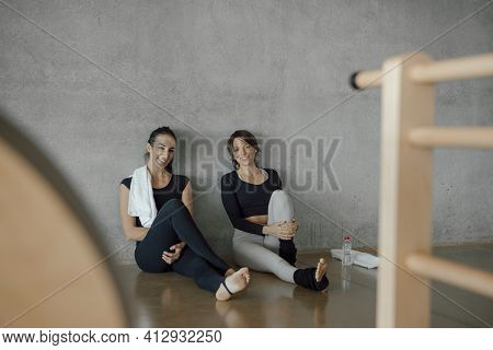 Smiling Caucasian Fit Women In Sport Clothing Sitting On The Floor Of A Gym Fitness Center, Looking