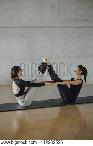 A Pair Sporty Yoga Women Doing Balance Exercise On Gray Stylish Industrial Background. Caucasian Bru