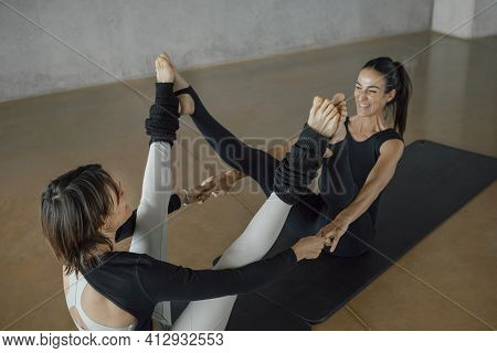 Top Angle Of A Happy Pair Sporty Yoga Women Balancing And Practicing Yoga In Studio. Caucasian Brune