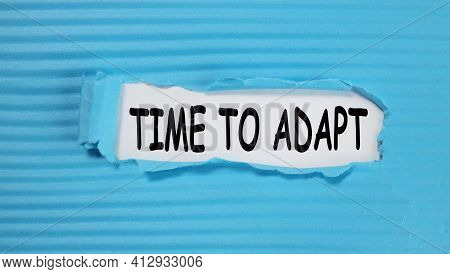 Time To Adapt. Text On White Paper Over Torn Paper Background.