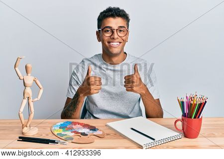 Young handsome african american man painter sitting palette and art manikin success sign doing positive gesture with hand, thumbs up smiling and happy. cheerful expression and winner gesture.