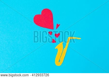 A Cutted Out Of Felt Saxophone From Which Hearts Flew Out, On A Blue Background. Flat Lay. Internati