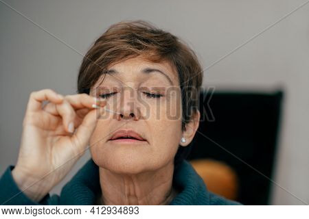 Portrait Senior Woman Taking A Auto Test For Covid-19 At Home With Antigen Kit. Introducing Nasal Sw