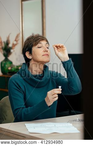 Portrait Senior Woman Sitting, Doing A Self Test For Covid-19 At Home With Antigen Kit. Introducing