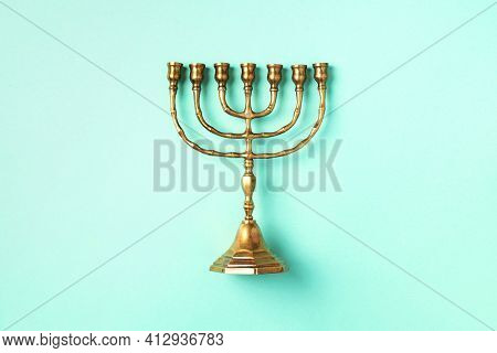 Golden Hanukkah Menorah On Blue Background. Jewish Holiday Banner With Copy Space. Ancient Ritual Re
