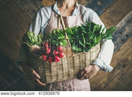 Woman Farmer Holding Basket Of Fresh Vegetables And Greens