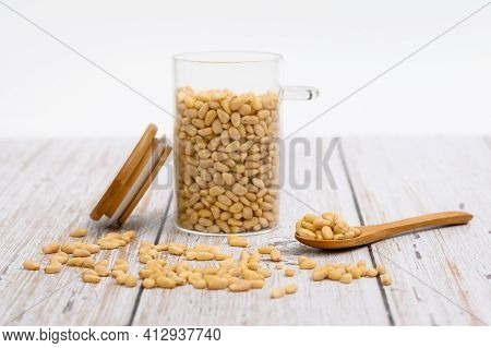 Wooden Spoon With Pine Nuts On The Table. Nearby Are Grains Of Nuts And A Glass Cup With Nuts. Selec