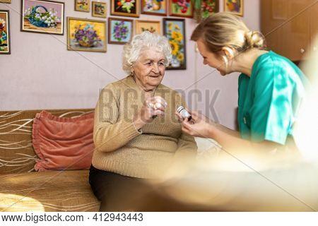 Female nurse reviewing prescription bottle with senior patient during home visit