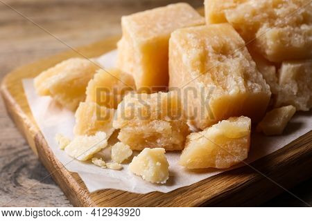 Pieces Of Delicious Parmesan Cheese On Wooden Board, Closeup