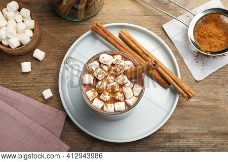 Glass Cup Of Hot Cocoa With Aromatic Cinnamon And Marshmallows On Wooden Table, Flat Lay