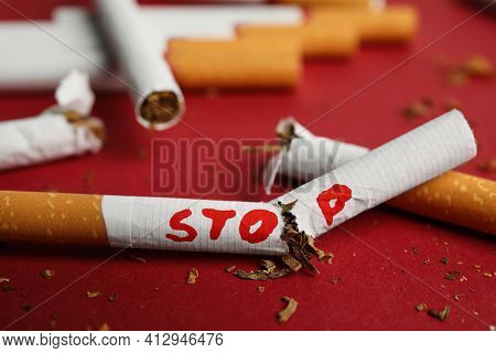 Broken Cigarette With Word Stop On Red Background, Closeup. Quitting Smoking Concept