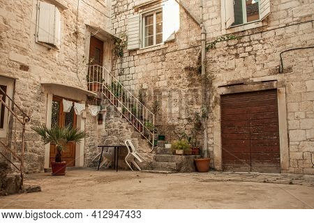 Beautiful View Of Croatian Town Houses. An Old Stone House With Stairs On Which There Are Many Flowe