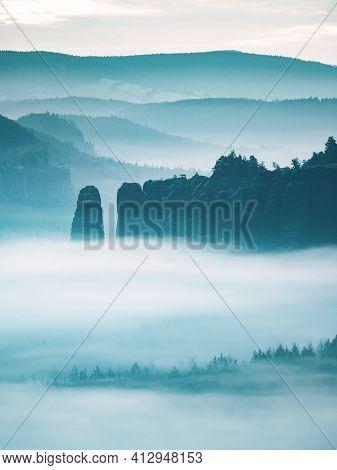 Mountain Peak Outline In Blue Night Mist.  Row Of Foggy Mountain Ranges In Sachsen Deutschland Park.